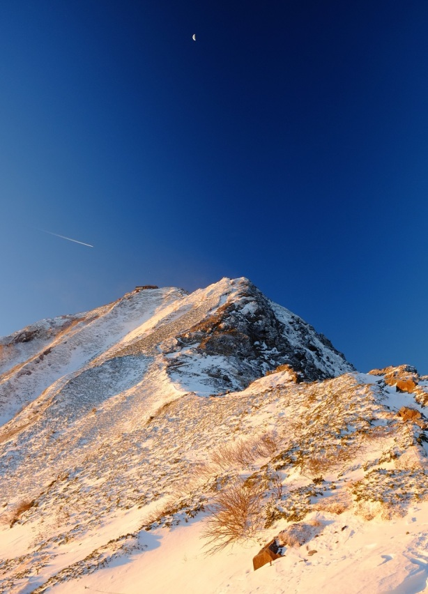 日の出直後の赤岳。少し朱に染まった雪山も神秘的です。飛行機雲もグッドタイミング。